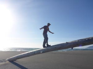 My brother walks up a log embedded in the Oregon sand -- an amazingly fun piece of playground equipment!